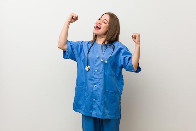 Jeune infirmière contre un mur blanc levant le poing après une victoire