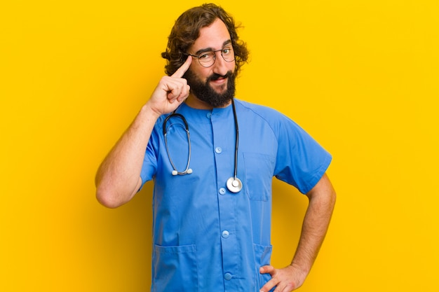 Jeune infirmière homme pensant contre le mur jaune