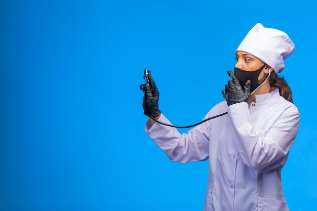 Jeune infirmière en masque noir et gants à la main vérifie le patient avec un stéthoscope tout en couvrant sa bouche