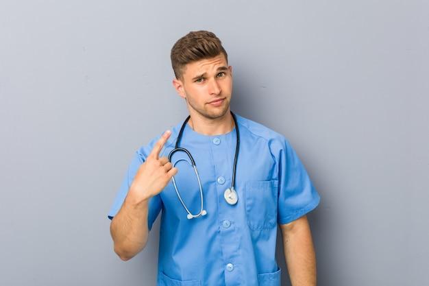 Jeune infirmière pointant du doigt vers vous comme si vous vous invitiez à vous rapprocher.