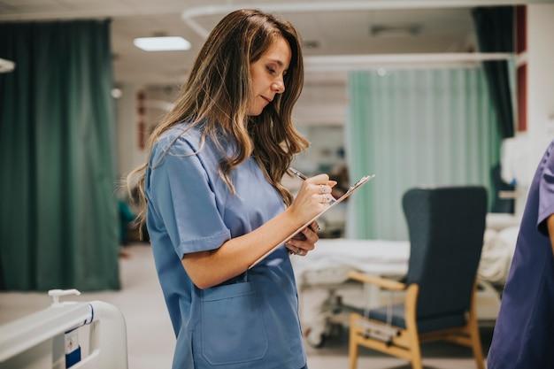 Jeune infirmière prenant des notes