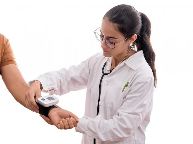 Jeune infirmière prenant la tension artérielle chez un patient avec un tensiomètre