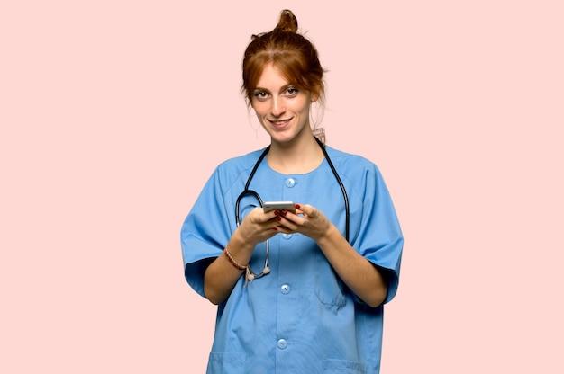 Jeune infirmière rousse envoie un message avec le téléphone portable sur fond rose