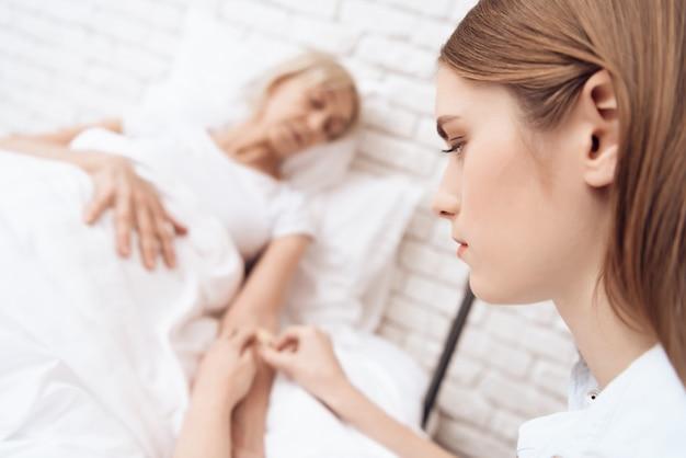 Une jeune infirmière sauve une vie femme âgée en clinique.