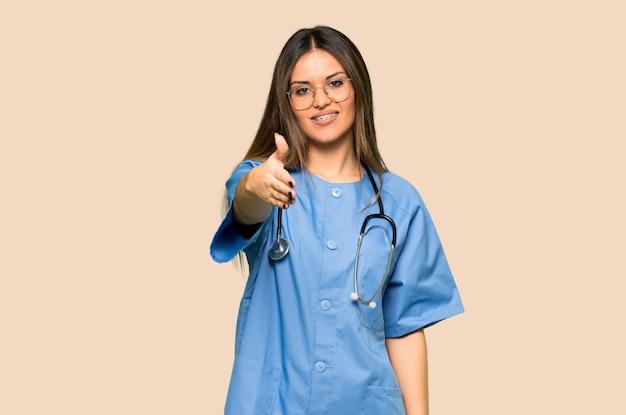 Jeune infirmière se serrant la main pour avoir conclu une bonne affaire sur un fond jaune isolé