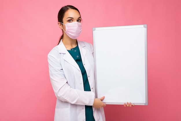 Jeune infirmière séduisante en masque protecteur tenant un tableau magnétique vide