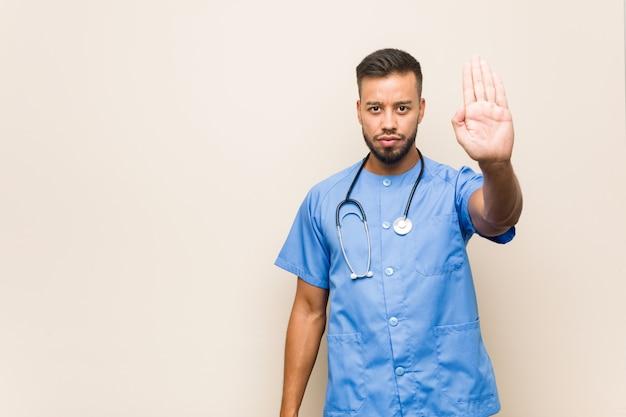 Jeune infirmière sud-asiatique homme debout avec la main tendue montrant le panneau d'arrêt