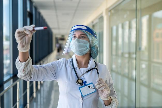 Jeune infirmière en tenue de protection et écran facial tenant un résultat de test sanguin positif pour covid-19 en laboratoire. pandémie