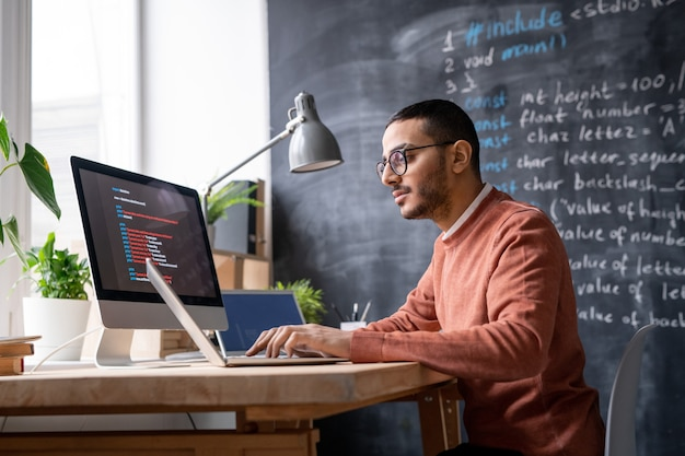 Jeune informaticien occasionnel assis devant un ordinateur portable au bureau et analysant les informations codées
