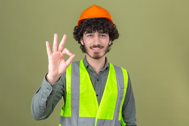 Jeune ingénieur beau barbu portant un casque de sécurité et gilet souriant faisant signe ok debout sur mur vert isolé