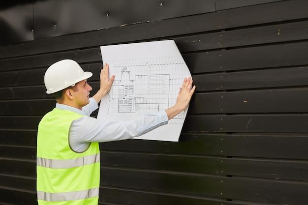 Jeune ingénieur en casque de travail et vêtements réfléchissants examinant le plan en se tenant debout à l'extérieur