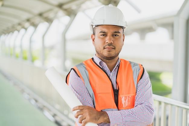 Jeune ingénieur civil asiatique tenant la paperasse debout au chantier de construction