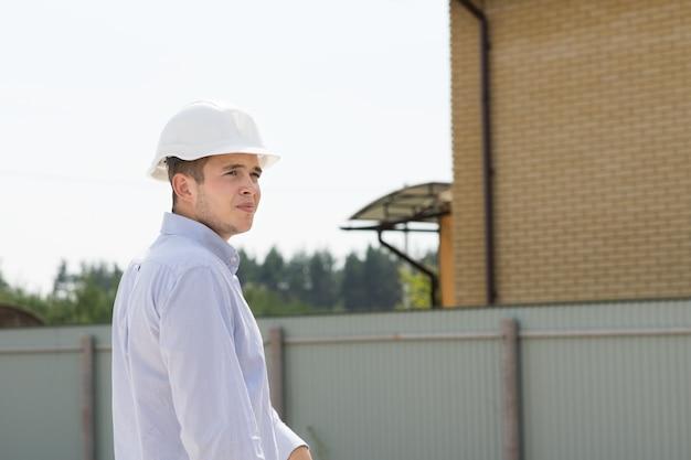Un jeune ingénieur civil masculin portant un casque blanc visite le site pour voir les progrès de la construction
