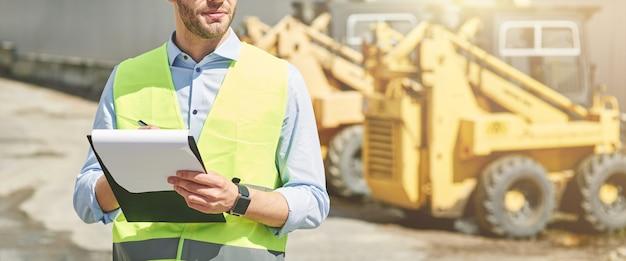 Jeune ingénieur civil portant un casque écrit un rapport en se tenant debout sur un chantier de construction