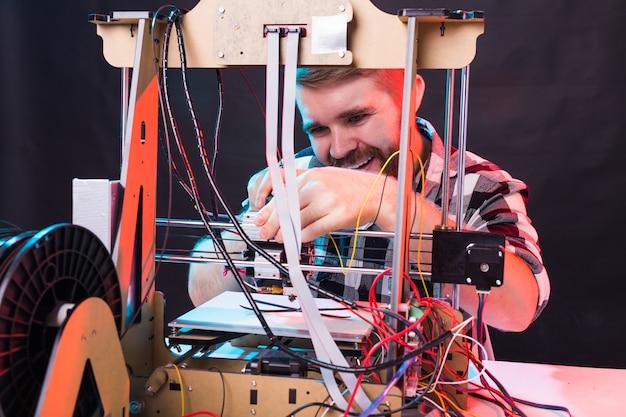 Jeune ingénieur designer masculin utilisant une imprimante en laboratoire et étudiant un prototype de produit, un concept de technologie et d'innovation.