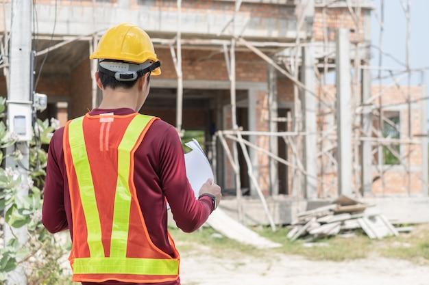 Jeune ingénieur devant une maison inachevée.