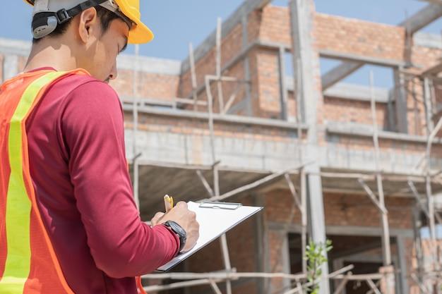 Un jeune ingénieur écrit sur un carton devant une maison inachevée.