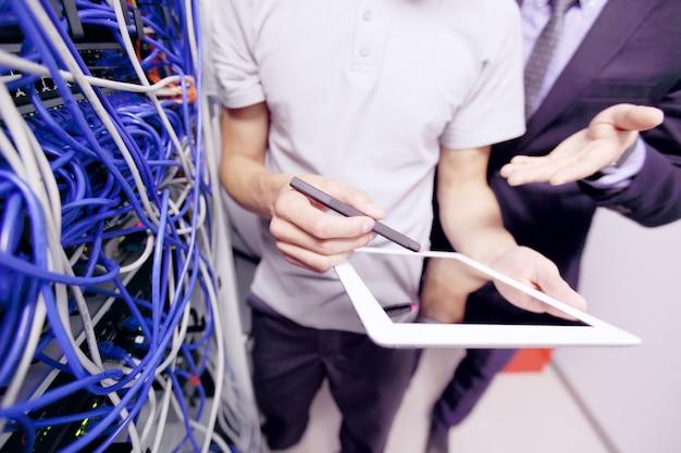 Jeune ingénieur et homme d'affaires dans la salle des serveurs réseau avec tablette numérique