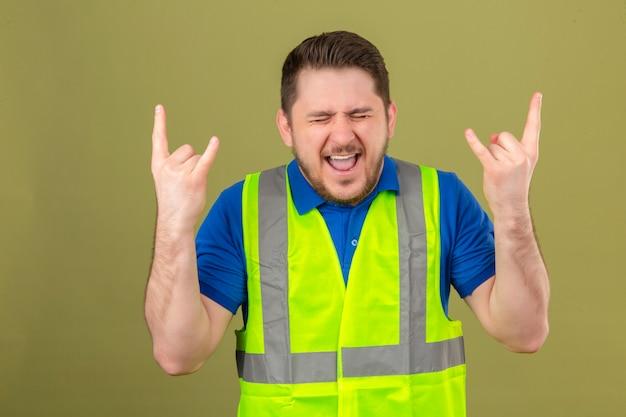 Jeune ingénieur homme portant un gilet de construction debout avec les yeux fermés avec une expression folle faisant le symbole de la roche avec les mains sur fond vert isolé