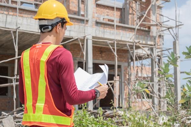 Un jeune ingénieur lit un plan devant une maison inachevée.