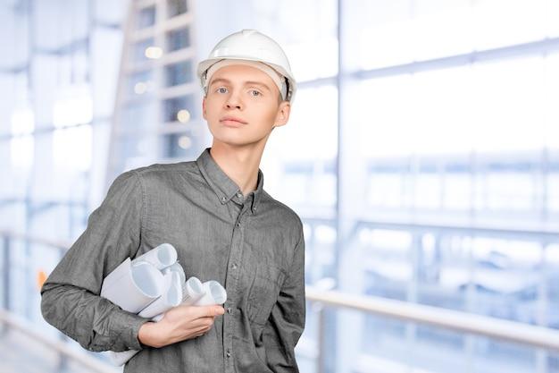 Jeune ingénieur masculin avec casque tenant des plans