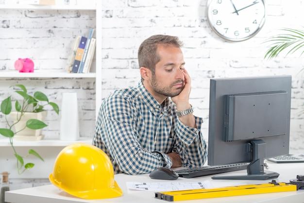 Un jeune ingénieur pensif devant son ordinateur