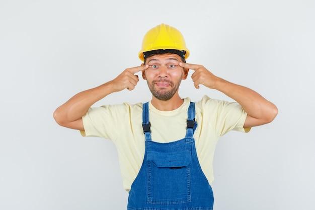 Jeune ingénieur plissant les yeux en uniforme et l'air fatigué, vue de face.