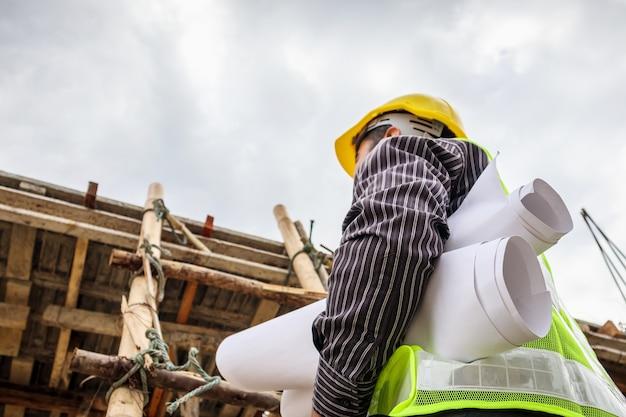 Jeune ingénieur professionnel en casque de protection et papier de plans sur place travaillant sur une échelle sur le chantier de construction de la maison