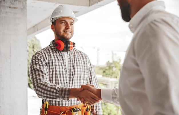 Jeune ingénieur de sexe masculin positif en casque de protection serrant la main du partenaire tout en se saluant sur le chantier de construction
