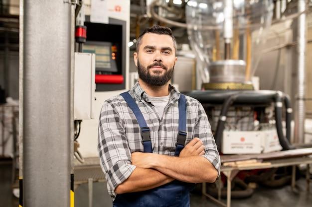 Jeune ingénieur de tube de traitement de polymère avec ses bras croisés par la poitrine debout