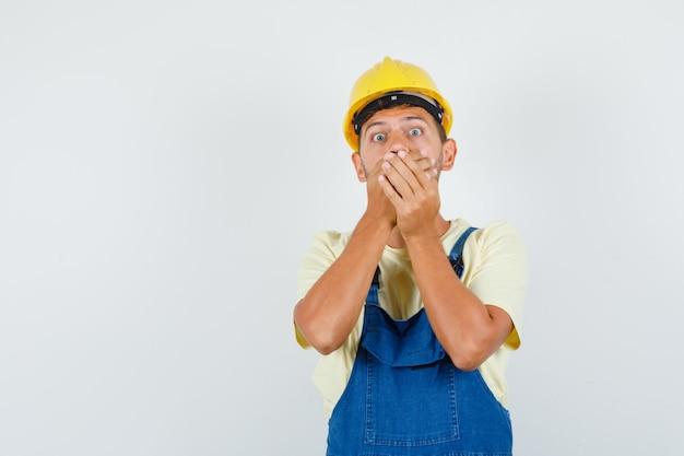 Jeune ingénieur en uniforme couvrant la bouche avec les mains et l'air effrayé, vue de face.
