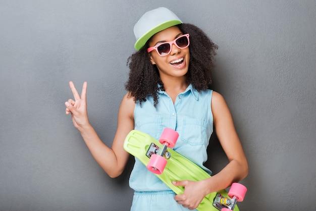 Jeune et insouciant. jolie jeune femme africaine tenant une planche à roulettes colorée et souriante en se tenant debout sur fond gris
