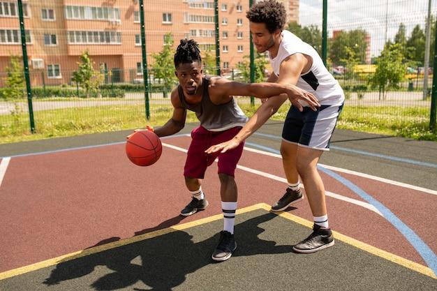 Jeune instructeur de basket-ball aidant un sportif africain avec l'un des exercices pendant l'entraînement en plein air sur le terrain