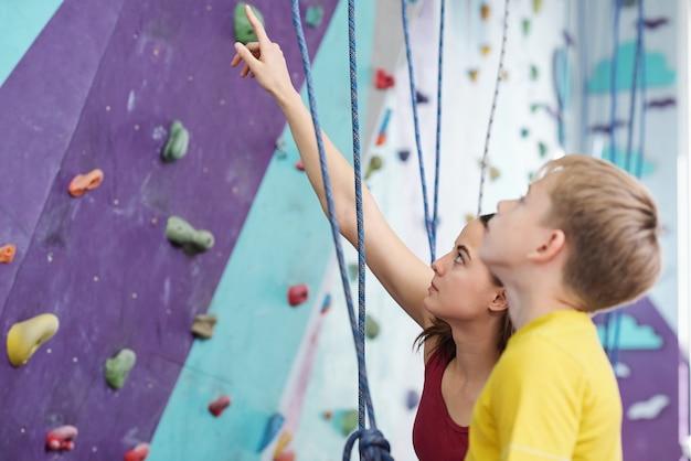Jeune instructeur pointant vers le haut tout en expliquant à l'écolier certains endroits dangereux sur le mur d'escalade avant l'entraînement