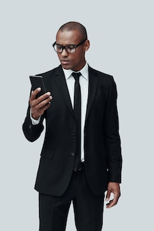 Jeune et intelligent. charmant jeune homme africain en tenue de soirée à l'aide d'un téléphone intelligent en se tenant debout sur fond gris