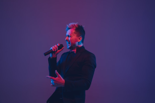 Jeune interprète de musicien caucasien chantant sur fond violet bleu dégradé à la lumière du néon