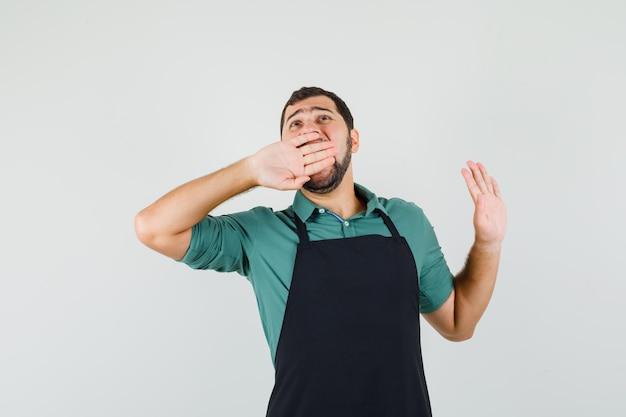 Jeune jardinier bâillant avec la main sur la bouche en t-shirt, tablier et ayant l'air fatigué. vue de face.
