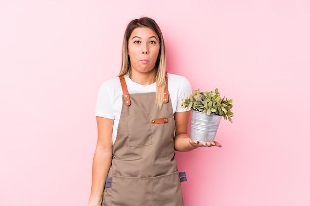 Jeune jardinier caucasien femme isolée hausse les épaules et les yeux ouverts confus.