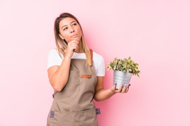 Jeune jardinier caucasien femme isolée à la recherche sur le côté avec une expression douteuse et sceptique.