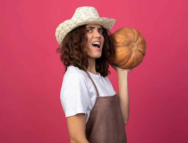 Jeune jardinier en colère en uniforme portant chapeau de jardinage tenant la citrouille