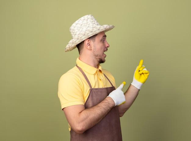 Jeune jardinier homme portant combinaison et chapeau en gants de travail pointant avec l'index en arrière à la confusion