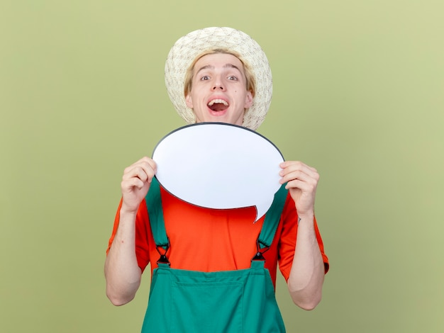 Jeune jardinier homme portant une combinaison et un chapeau tenant un signe de bulle de discours vierge furtivement sur souriant joyeusement debout sur fond clair