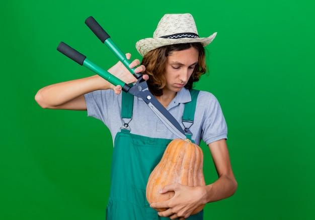 Jeune, jardinier, homme, porter, combinaison, et, chapeau, tenue, citrouille