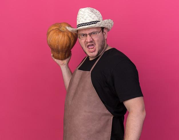 Jeune jardinier mâle en colère portant chapeau de jardinage tenant citrouille isolé sur mur rose