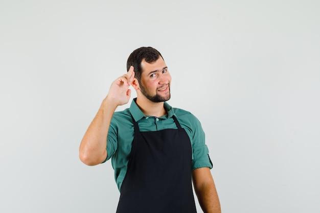 Jeune jardinier montrant un geste d'adieu en t-shirt, tablier et l'air reconnaissant, vue de face.
