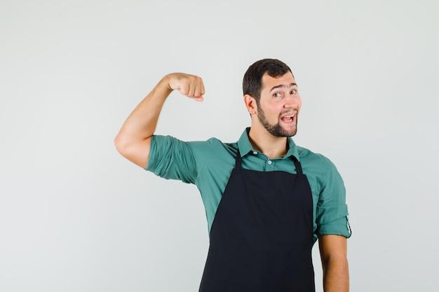 Jeune jardinier montrant les muscles de ses bras en t-shirt, tablier et regardant joyeux, vue de face.