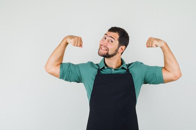 Jeune jardinier montrant les muscles de ses bras en t-shirt, tablier et semblant joyeux, vue de face.