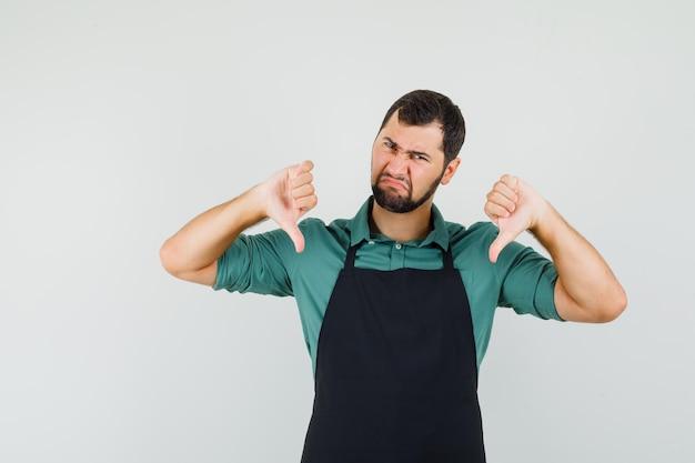Jeune jardinier montrant le pouce vers le bas en t-shirt, tablier et l'air mécontent. vue de face.