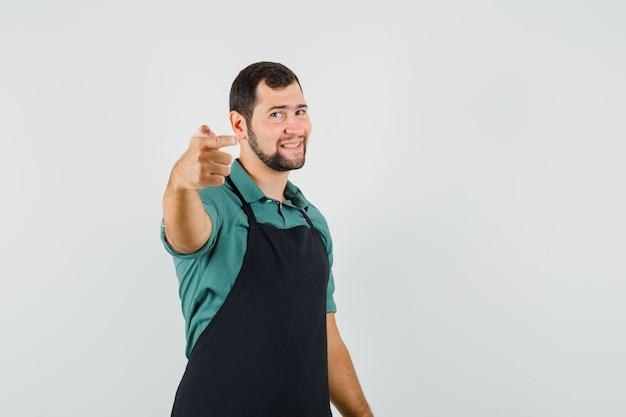 Jeune jardinier pointant vers l'avant en t-shirt, tablier et semblant positif, vue de face.