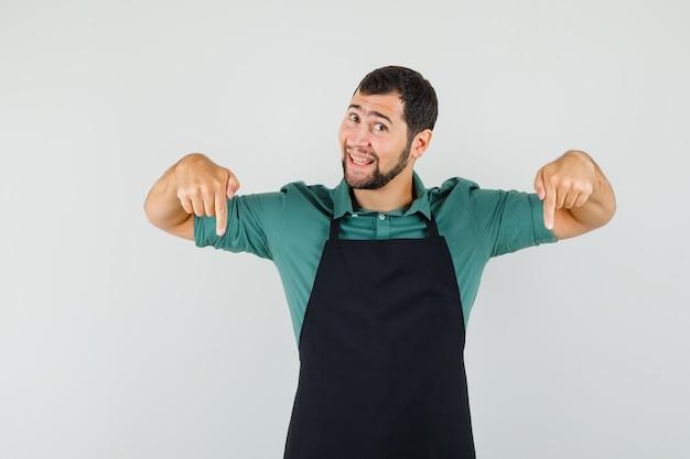 Jeune jardinier pointant vers le bas en t-shirt, tablier et semblant optimiste. vue de face.